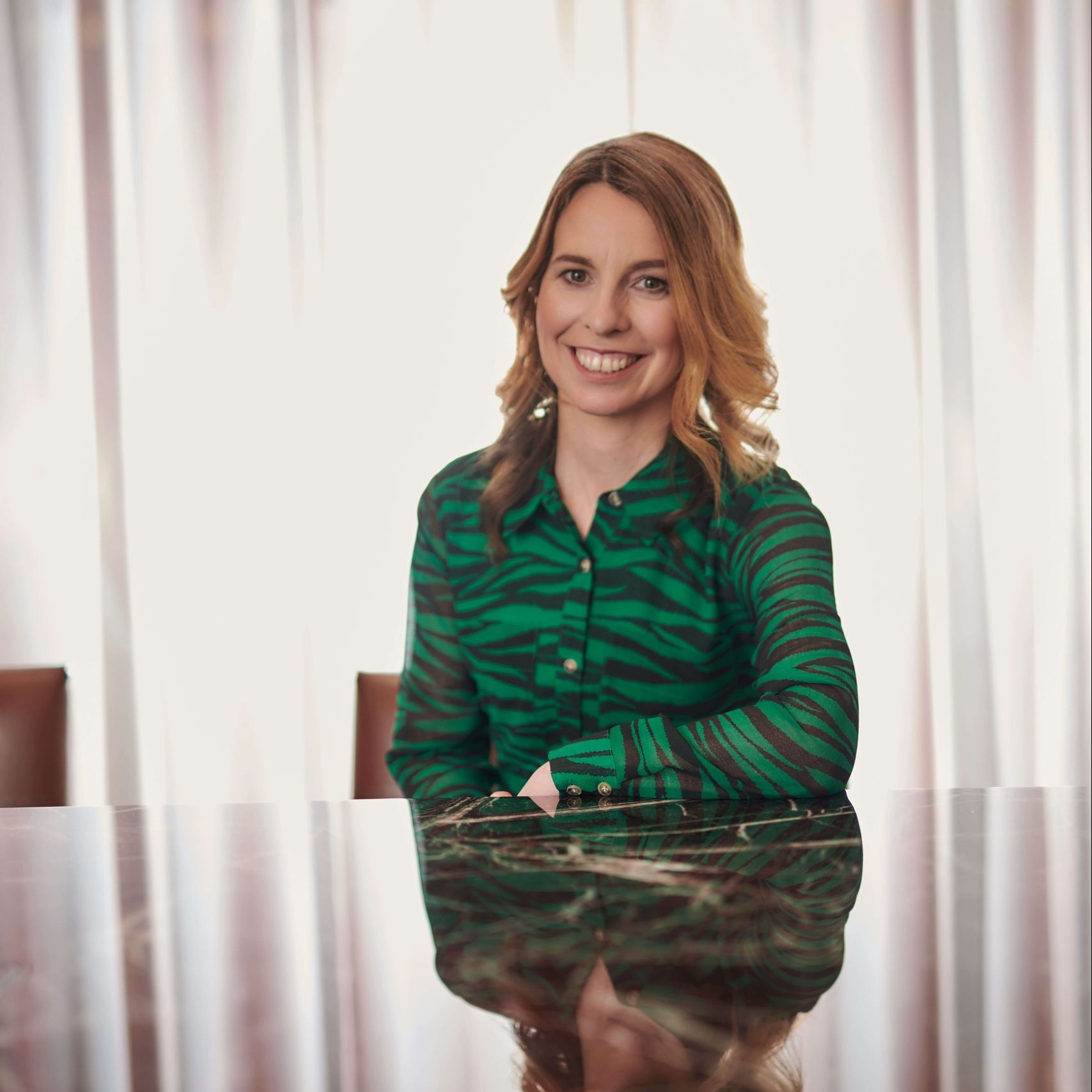 Katy Turner, in charge of PR for Meteoric Marketing, sitting at a table looking a the camera